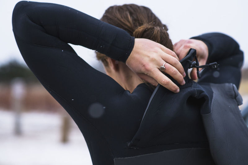 Rear view of woman photographing against black background