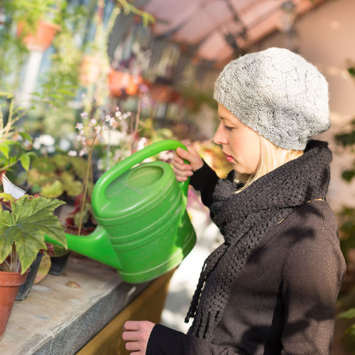 Side view of woman watering plants shop