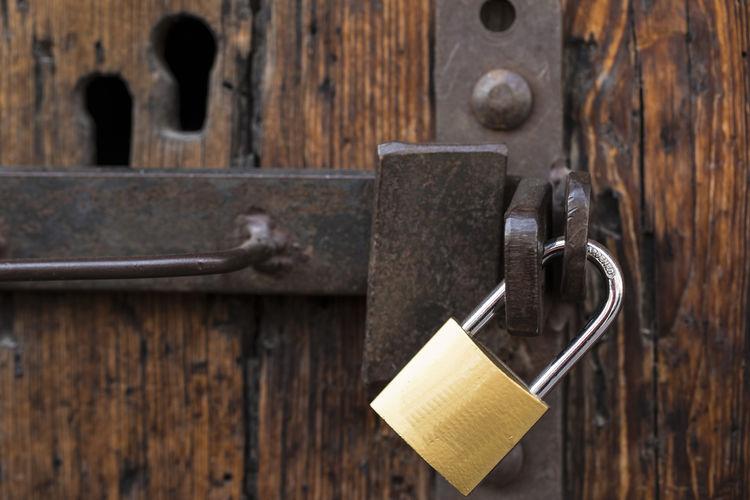 Close-up of golden padlock on wooden door
