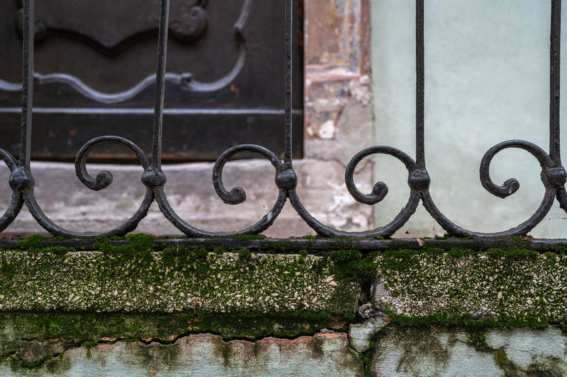 Close-up of metal railing against wall