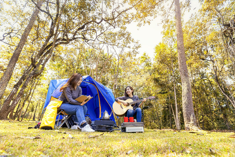 Happy friends with book and guitar camping in forest
