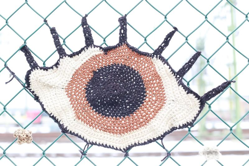 Eye Full Frame Crocheted Crocheting Fences Iris Focus On Foreground Focus Looking Eye Yarn Bombing Yarn Handmade Art Creative Power Creating Art Creative Creativity Production Chainlink Fence Metal Protection Security Safety Pattern Day No People Outdoors Sky Close-up