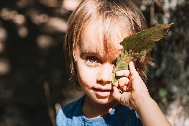 Portrait of girl holding leaf