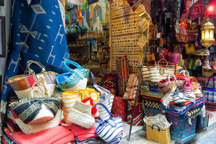 View of beautiful and colorful bags and rugs in the Medina in Tunis, Tunisia Leather Medina Tunis Tunisia Accessories Africa Arabic Business Cushions  Decoration For Sale Lamp Lamps Large Group Of Objects Market Market Stall Multi Colored Ornaments Rugs Sale Seller Store Street Traditional Wallets