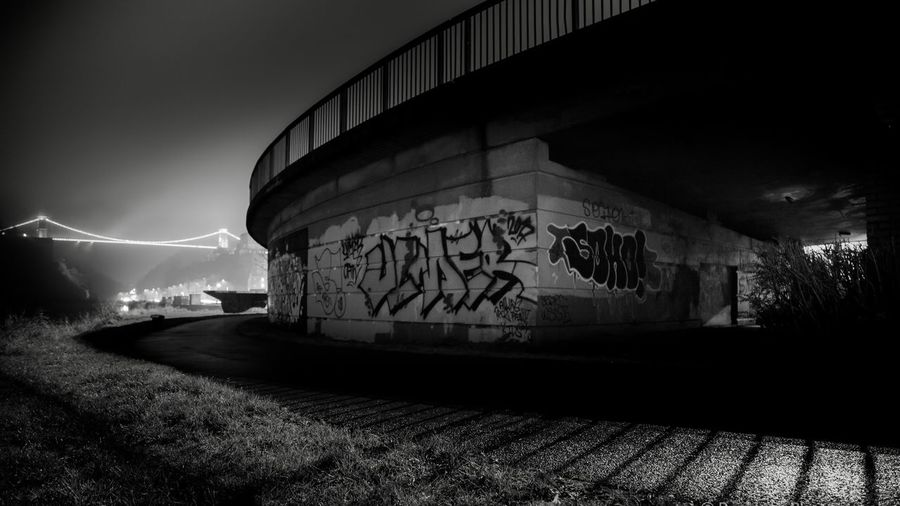 Graffiti covered bridge EyeEmNewHere Shadows & Lights Suspension Bridge Bridge Blackandwhite Bnw Photo Street Art Streetphotography Art City Life Cityscape City Night Photography Light And Shadow Nightphotography Night Graffiti Built Structure Architecture Night Outdoors No People Illuminated Building Exterior EyeEmNewHere The Graphic City