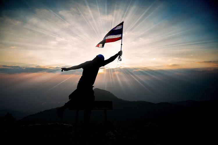 Silhouette person holding thai flag while standing against sky during sunset