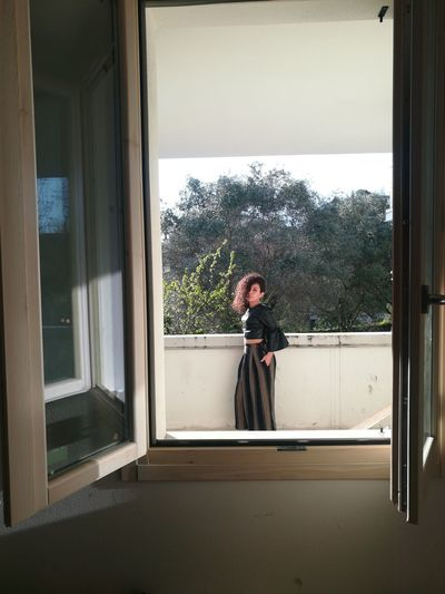 Woman standing by retaining wall seen through window