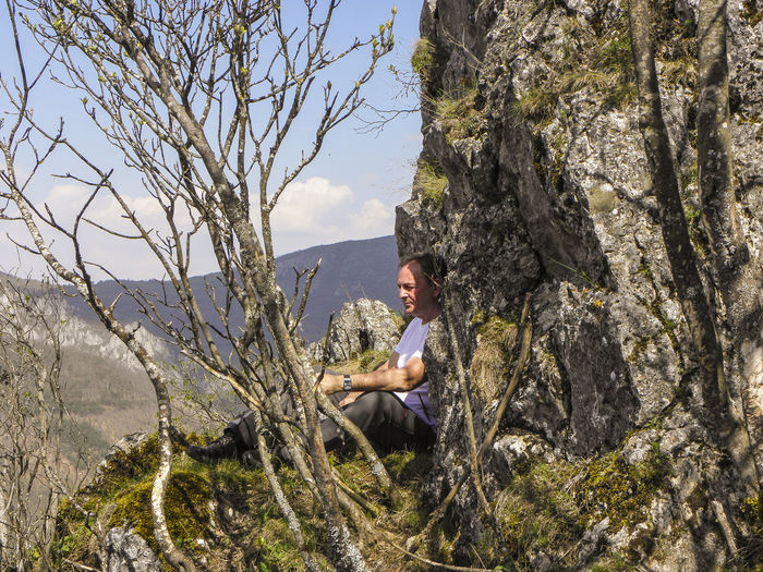 Side view of young man sitting on rock
