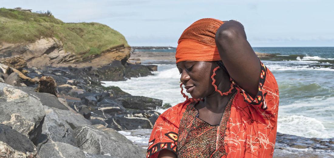African woman with orange dress on the cliffs by the sea in sekondi-takoradi ghana west africa