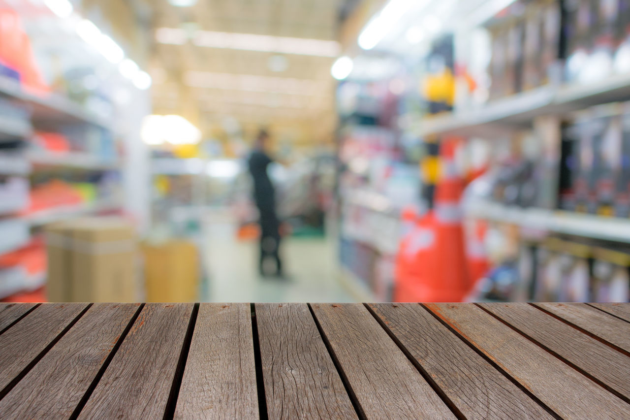 wood - material, retail, store, indoors, incidental people, shopping, one person, supermarket, focus on foreground, day, lifestyles, selective focus, market, choice, real people, consumerism, shelf, architecture