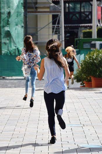 Full length of girls walking on sidewalk in city