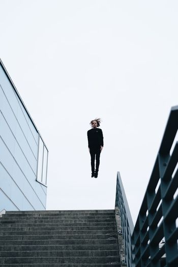 Low angle view of person on staircase against building