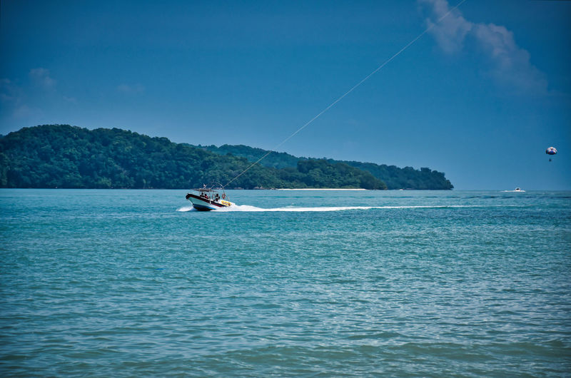 Parasailing on the waves of the azure andaman sea under the blue sky near the shores of cenang beach