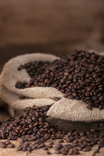 Close-up of roasted coffee beans on wooden table