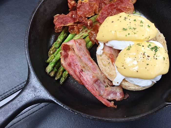 High Angle View Of Eggs Benedict With Meat And Asparagus In Skillet