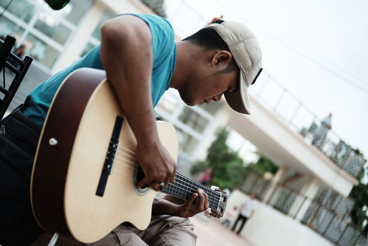Tilt shot of street musician playing guitar in city