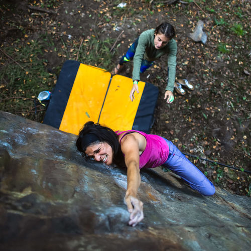 High angle view of woman climbing on boulder