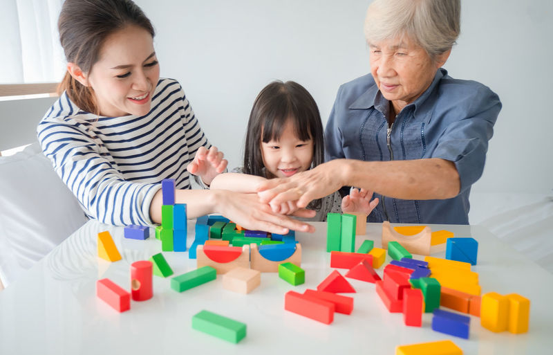 Multi-generation Female members of a family play wooden cubes colour (Geometric ladder) together with their grandmother, family time Childhood Child Family Females Women Girls Indoors  Togetherness Bonding Parent Mother Leisure Activity Portrait Front View Adult Smiling Headshot Casual Clothing Lifestyles Daughter Innocence Grandchild