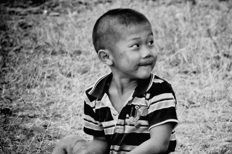 Portrait of boy sitting on field