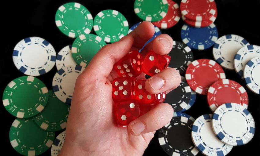 Cropped Hand Holding Dice On Gambling Chips