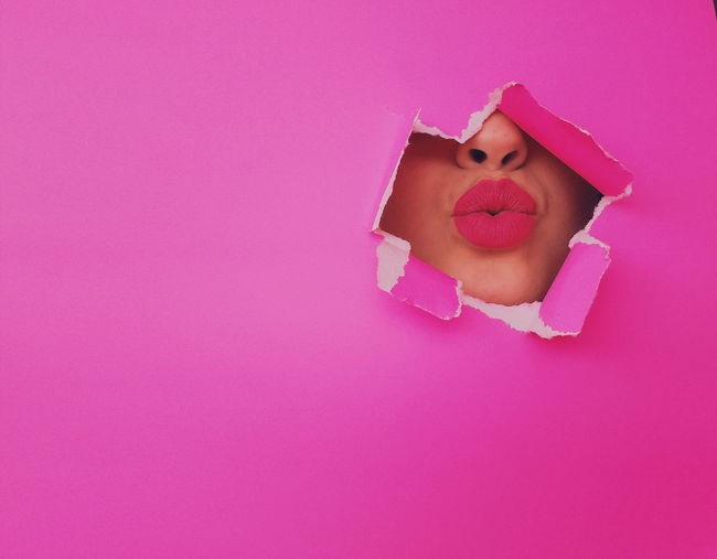 Close-up portrait of woman with pink petals on background