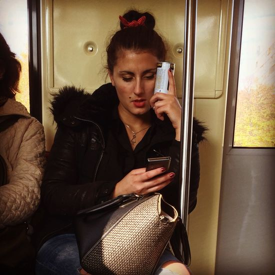 Young Woman Using Mobile Phone And Holding Drink Can While Traveling In Subway Train