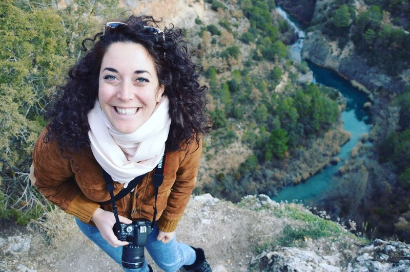 High angle portrait of cheerful woman photographing on cliff