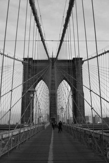 Brooklyn Bridge / New York Built Structure Architecture Bridge Bridge - Man Made Structure Transportation Connection Real People Engineering Sky Arch Travel Destinations Travel Tourism Men Outdoors New York City 2005 Blackandwhite Manhattan Americana Symbol Architecture Man Made Object