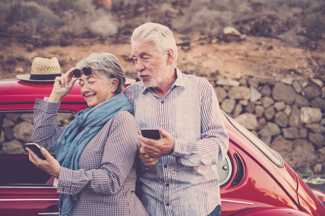 Elderly couple with hat, with glasses, with gray and white hair, with casual shirt, on vintage red car on vacation enjoying time and life. With a cheerful mobile phone smiling immersed in the windy spring weather of the Canary Islands Complicity Couple Friends Fun Love Man Mobile Phone Vacations Vintage Style Woman Curiosity Friendship Future Happyness Message Old Car Senior Adult Senior Man Senior Woman Taking Selfies Technology Tenderness Togetherness Usino Phone White Hair