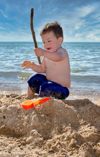 Boy sitting on shore at beach against sky
