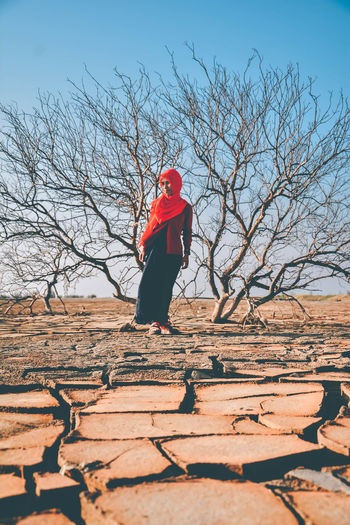 Arid. One Person Real People Bare Tree Lifestyles Tree Full Length Leisure Activity Nature Sky Outdoors Red Women Land Dead Tree Summer Arid Backgrounds Day Muslimah Sunlight Clothing