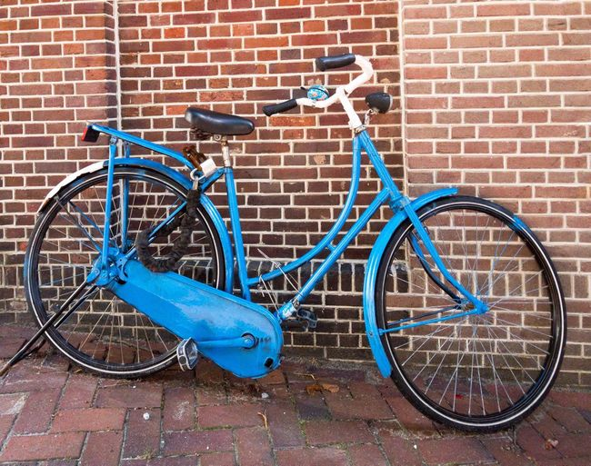 Blue bicycle in front of red wall Bicycle Brick Wall Blue Stationary Outdoors Day No People Bicycle Rack Red For Ladys Retro Vintage Netherland Still Life Background Female Holland Bike