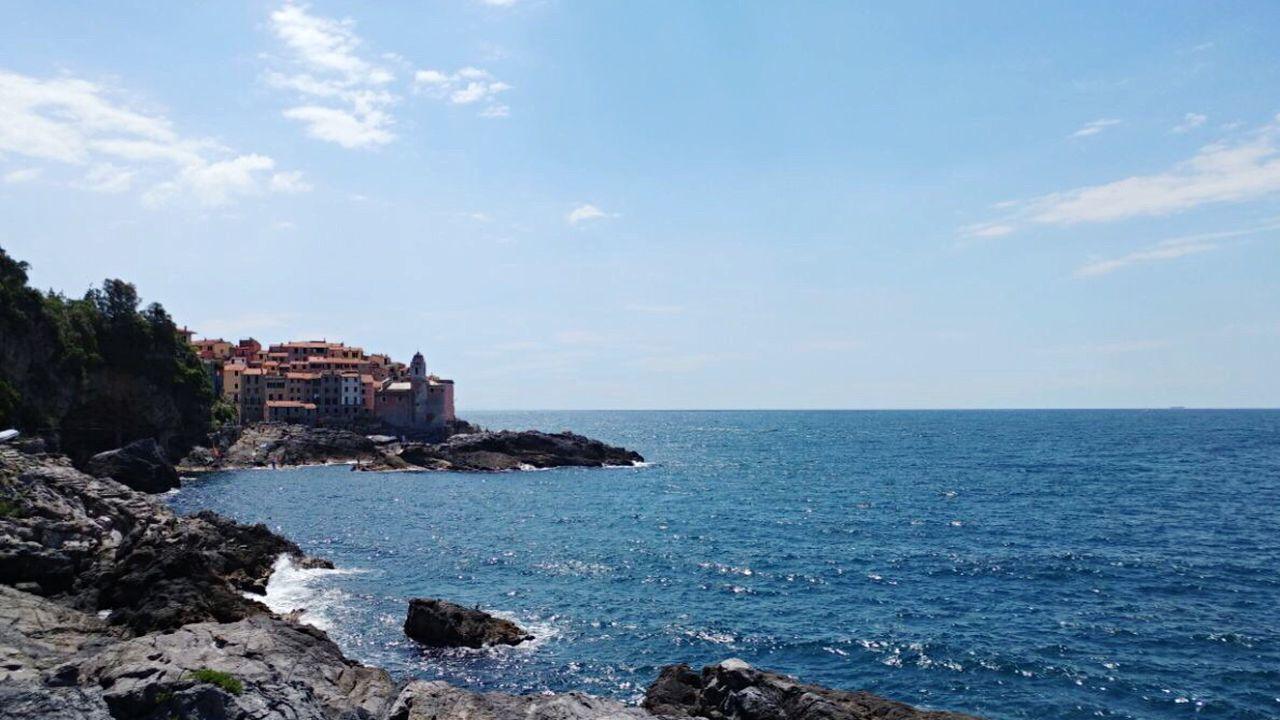 SEA BY ROCKS AGAINST SKY