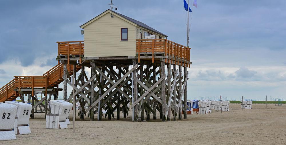 Beach huts by sea against sky