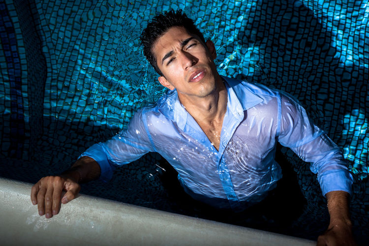 Portrait of young man sitting in swimming pool