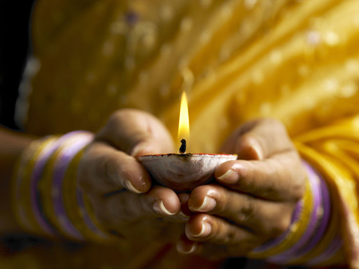 close up of indian woman with traditional clothing holding oil lamp during deepavali Celebration Diwali Ethnicity Flame Indian Woman Traditional Clothing Accessory Burning Clay Lamp Close-up Deepavali  Diwali Diya - Oil Lamp Festive Of Lights Flame Heat - Temperature Holding Human Body Part Human Hand Illuminated Light And Shadow Night Oil Lamp Real People Sari