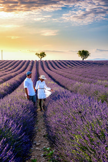 Couple standing amidst flowering plants against sky