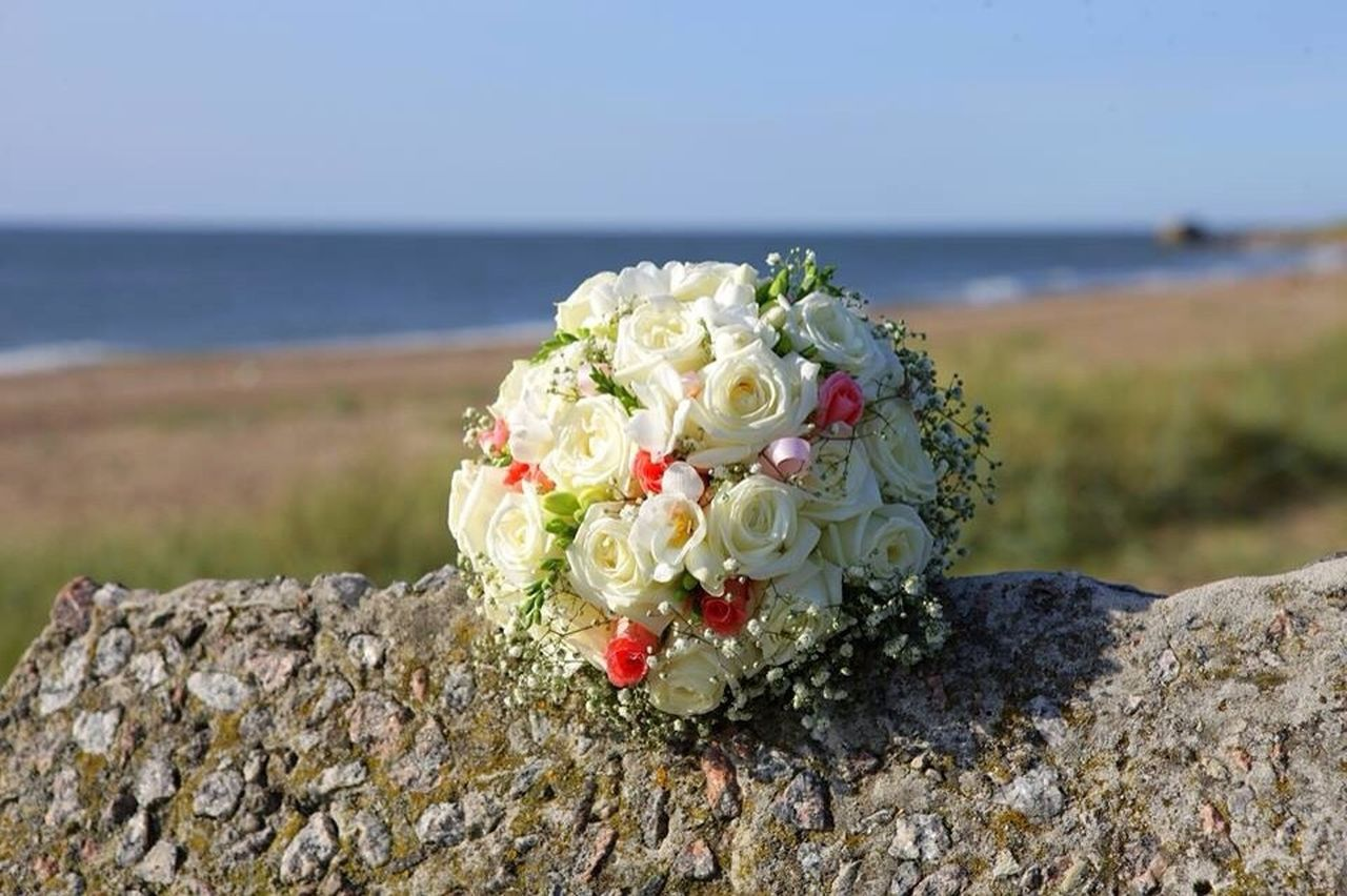 CLOSE-UP OF ROSE BOUQUET ON ROCK