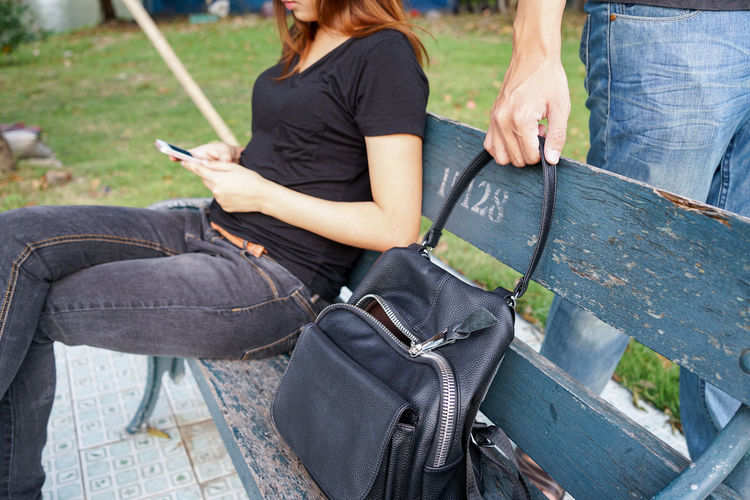 Mugger stealing purse of woman using mobile phone at bench