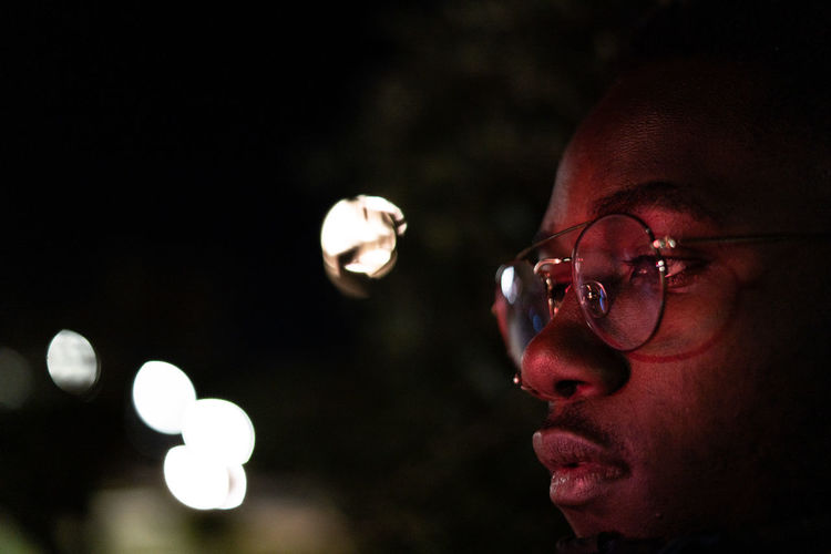 Close-up portrait of young man looking away at night