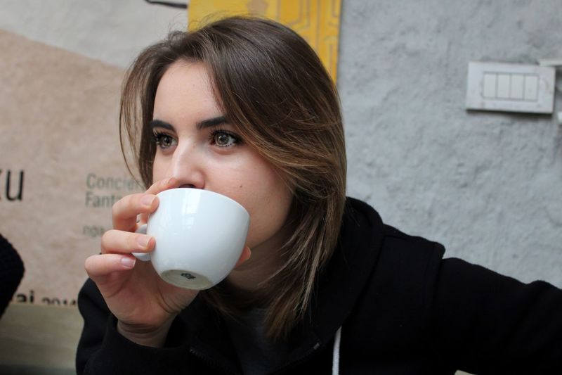 Close-up of young woman drinking coffee at cafe