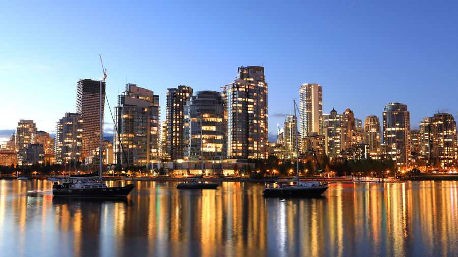Illuminated buildings by river against clear sky