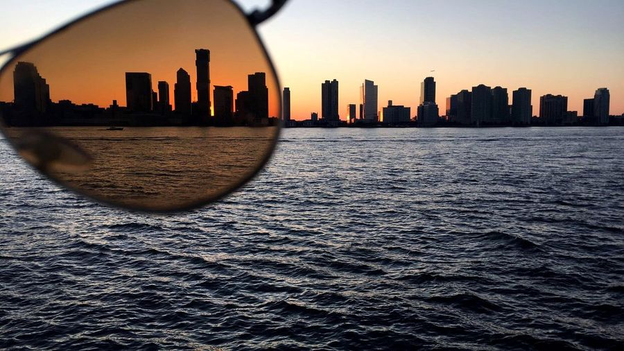 Silhouette Buildings By River Seen Through Sunglasses During Sunset