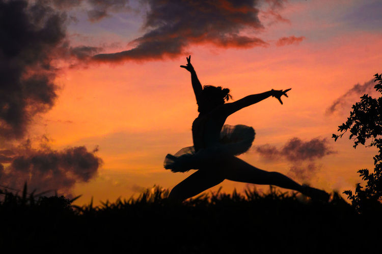 Silhouette ballet dancer jumping while dancing against sky during sunset