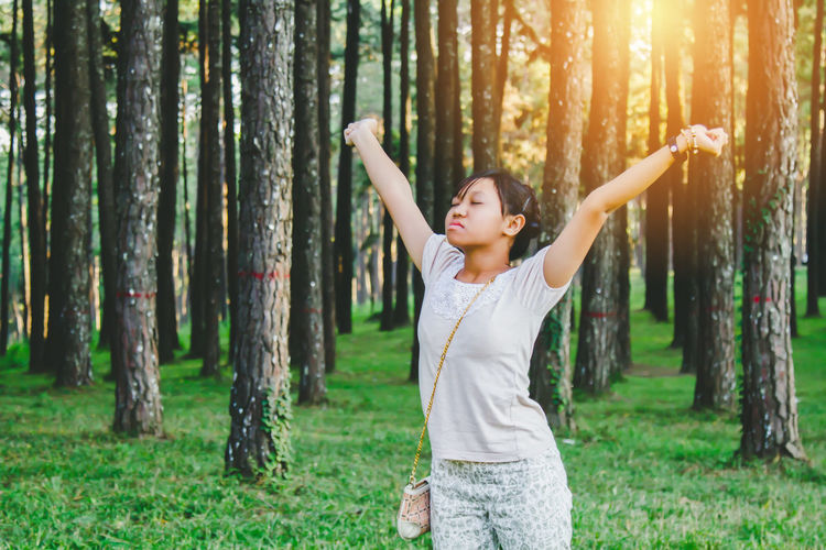 Young woman with arms outstretched standing against trees in forest