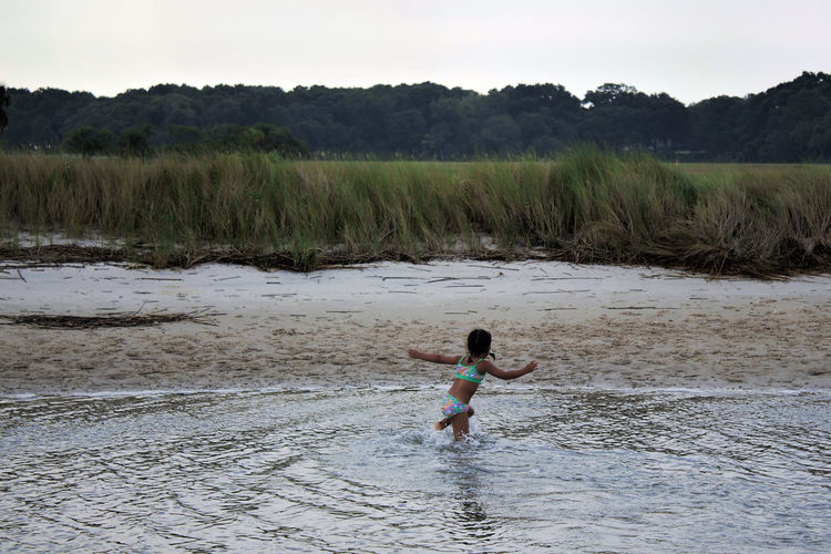 Rear view of girl running in water at beach
