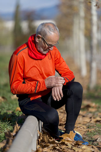 Senior runner man resting at the park while monitoring his exercise Athlete Exercising Man Pulse Running Sitting Active Aged Device Gear Healthy Healthy Lifestyle Jogging Lifestyles Male Outdoors Park Running Water Smartwatch Sport Sportswear Trainning Trendy Urban Watch