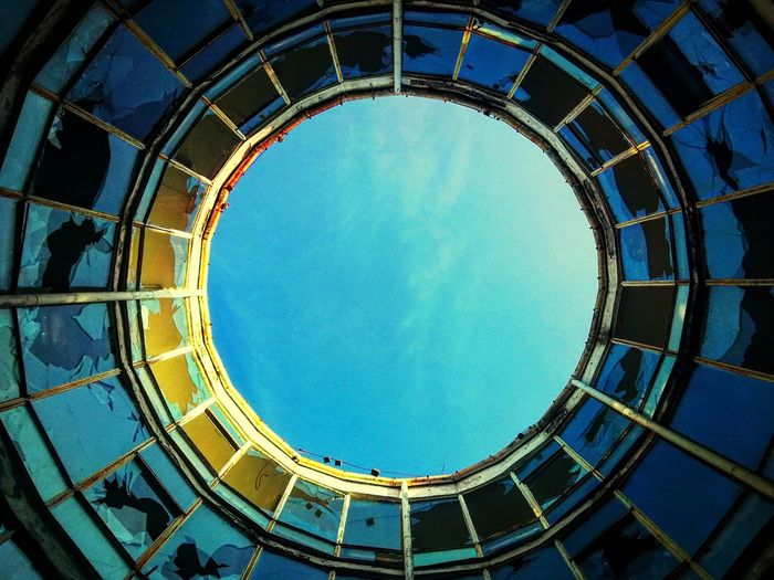 Directly Below Shot Of Blue Sky Seen Through Circular Ceiling