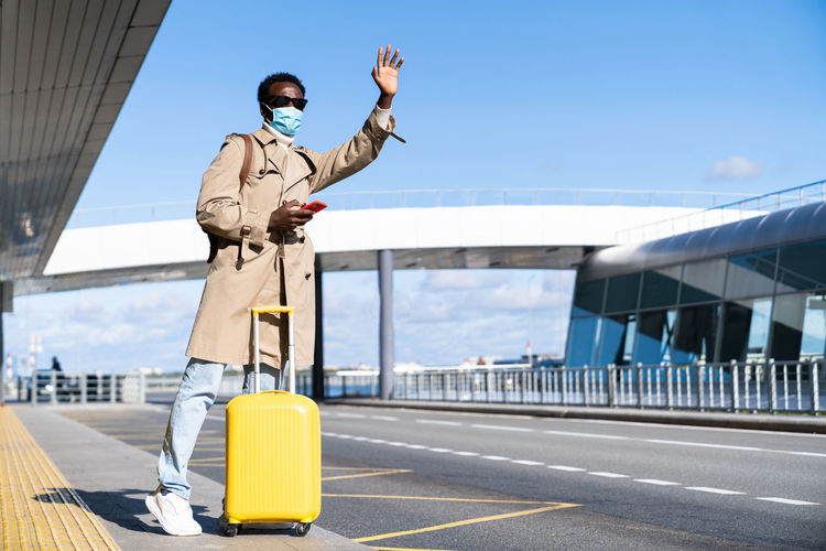 Full length of man wearing mask standing at airport