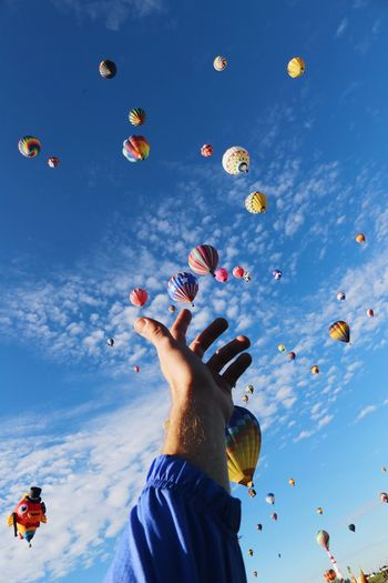 Optical Illusion Of Hand Touching Hot Air Balloons Flying Against Sky